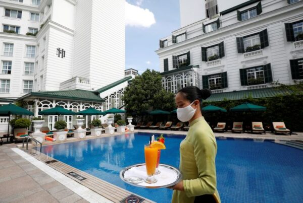 © Reuters. FILE PHOTO: A woman wearing a protective mask carries glasses of fruit juice by the swimming pool of the Sofitel Legend Metropole hotel in Hanoi